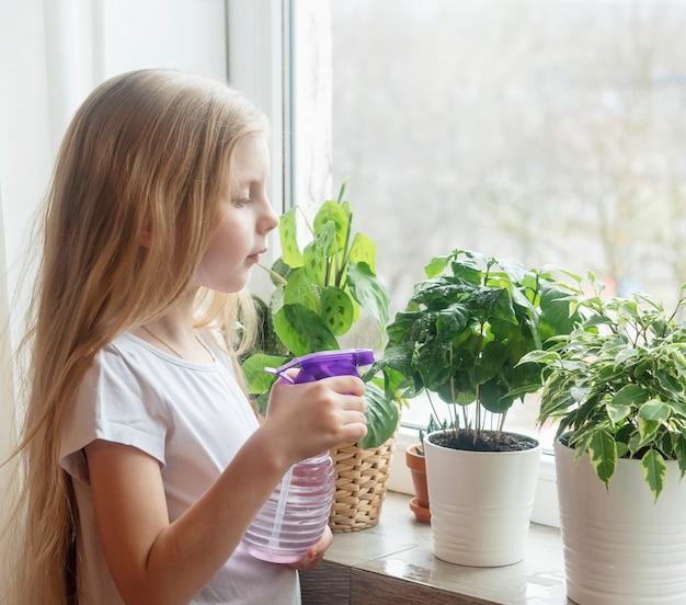 Bambina che innaffia le piante d'appartamento nella sua casa