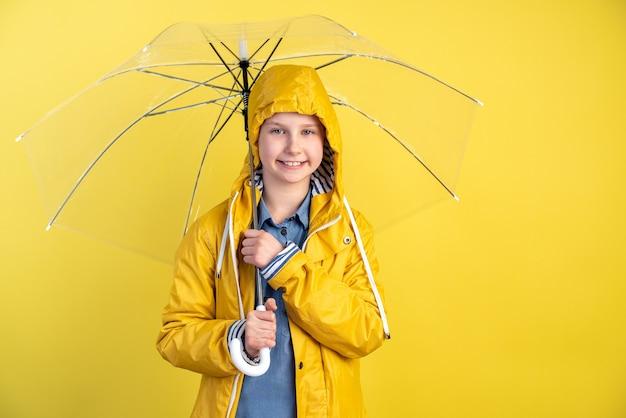 Bambina in un impermeabile impermeabile e con un ombrello su una parete gialla