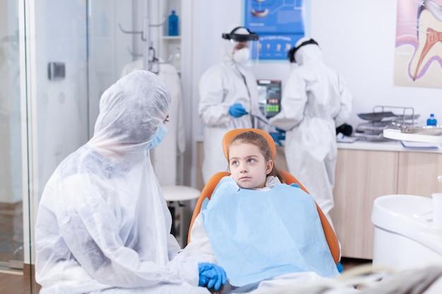 Bambina che indossa tuta in studio dentistico in attesa di cure odontoiatriche seduto sulla sedia. stomatologo durante il covid19 che indossa una tuta in dpi facendo la procedura dei denti del bambino seduto sulla sedia.