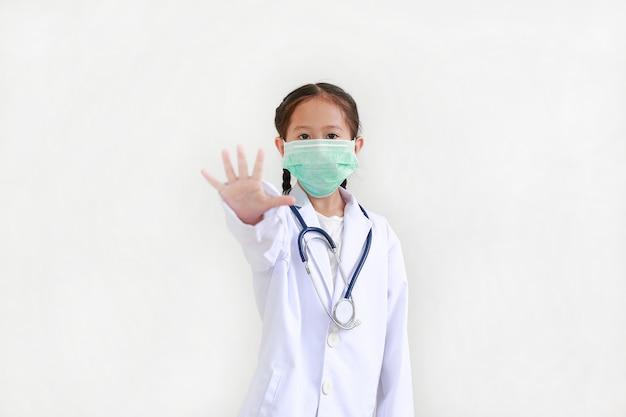 Bambina indossa l'uniforme di un medico e mascherina medica