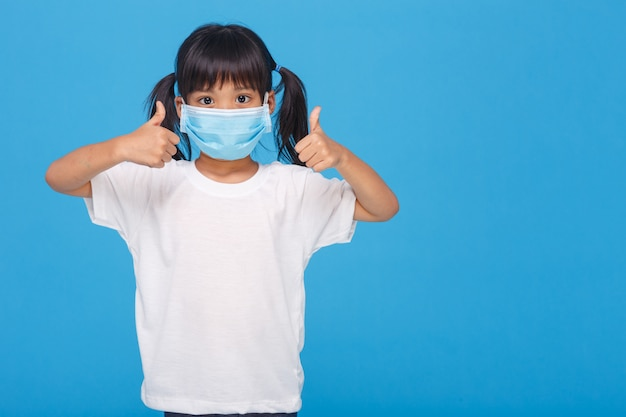 Maschera di protezione da portare della bambina che mostra i pollici in su