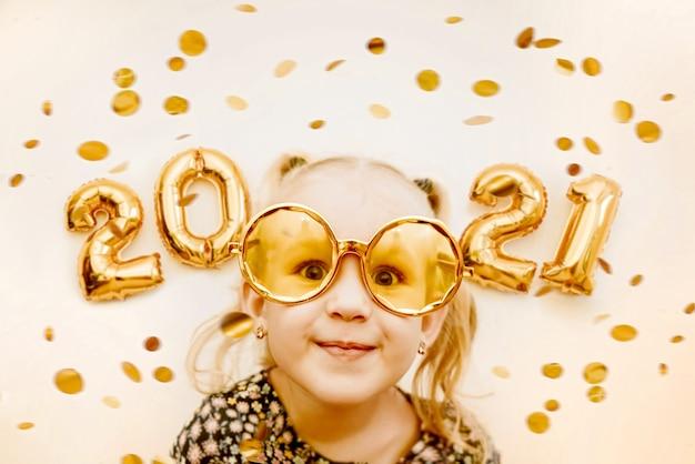 Bambina indossa occhiali mascherati d'oro sorridente, scherzare