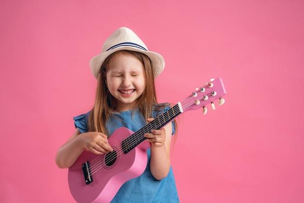 Bambina che indossa un cappello e una chitarra ukulele