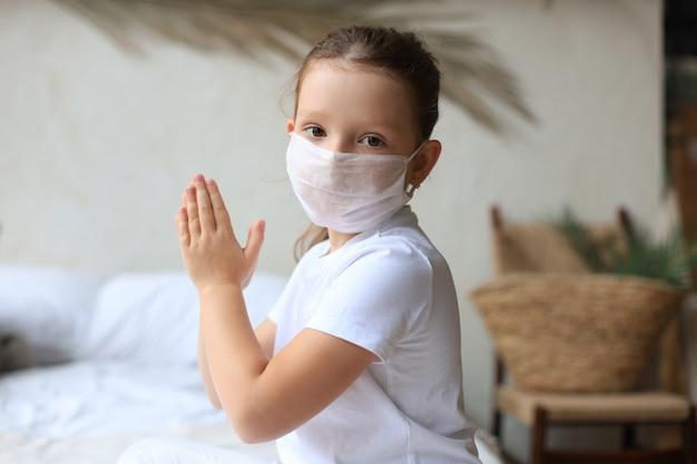 Bambina che indossa una maschera per proteggere covid-19. prega al mattino per un nuovo giorno di libertà per il virus corona mondiale. la mano della bambina che prega per ringraziare dio