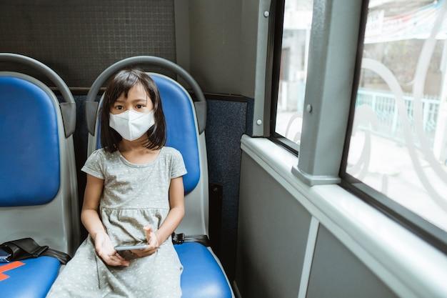 Una bambina che indossa una maschera si siede su una panchina con in mano un cellulare sull'autobus durante il viaggio