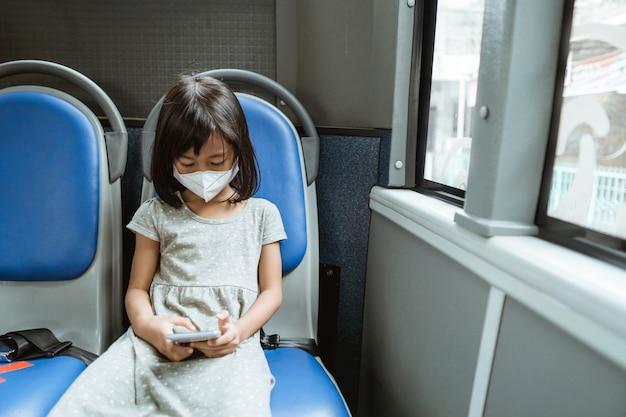Una bambina che indossa una maschera si siede su una panchina mentre utilizza uno smartphone sull'autobus durante il viaggio