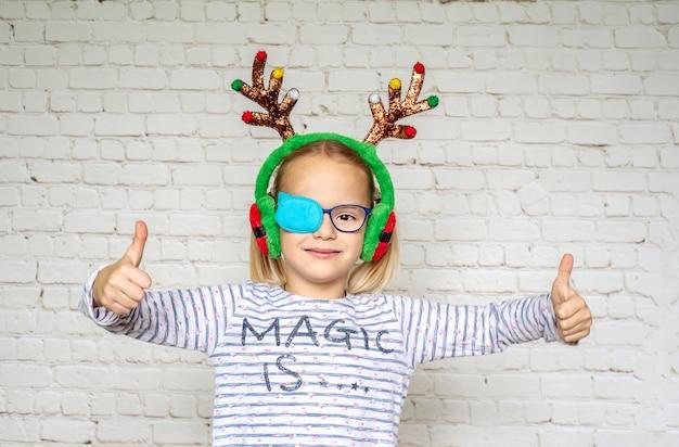 Bambina che indossa occlusore e corna di renna natalizia, trattamento dell'ambliopia e problemi di vista