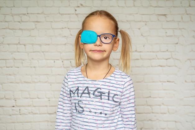 Bambina che indossa occlusore e occhiali da vista, trattamento dell'ambliopia e problemi di vista