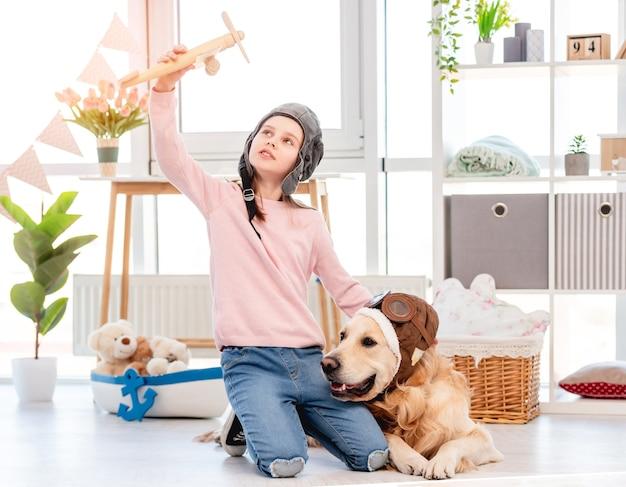 Bambina indossa cappello pilota seduto sul pavimento con il cane golden retriever in occhiali pilota e gioca con l'aereo di legno