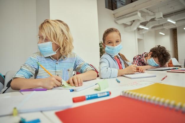 Bambina che indossa una maschera protettiva che guarda la telecamera i bambini delle scuole elementari seduti insieme