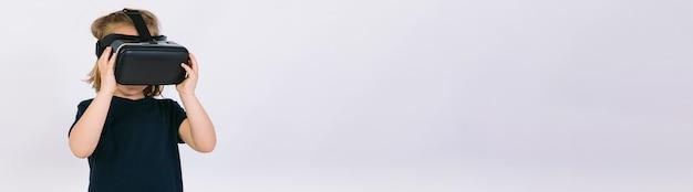 Bambina indossa occhiali per realtà virtuale, su sfondo bianco