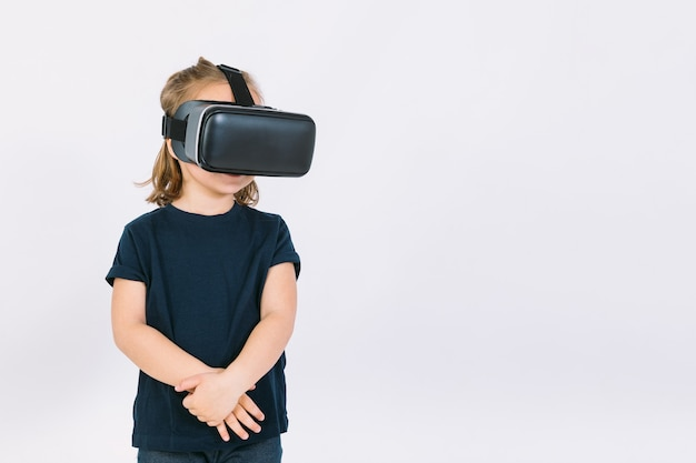 Bambina indossa occhiali per realtà virtuale con le braccia incrociate, su sfondo bianco