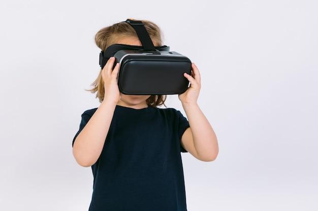 Bambina indossa occhiali per realtà virtuale con le mani tenere gli occhiali di protezione su sfondo bianco