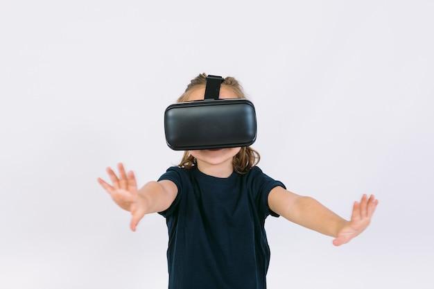 Bambina indossa occhiali per realtà virtuale con le mani cercando di toccare qualcosa virtualmente, su sfondo bianco