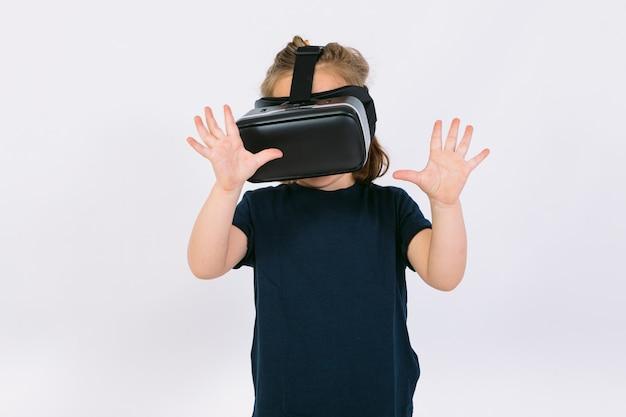 Bambina che indossa occhiali per realtà virtuale con le mani che cercano di toccare qualcosa virtualmente