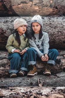 La bambina sussurra un segreto alle sue sorelle sedute sui tronchi.