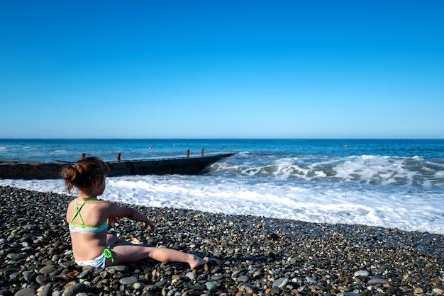 La bambina in costume da bagno bianco seduta sul berugu del mare lancia pietre nell'acqua. il concetto di vacanza estiva per bambini al mare. vacanza