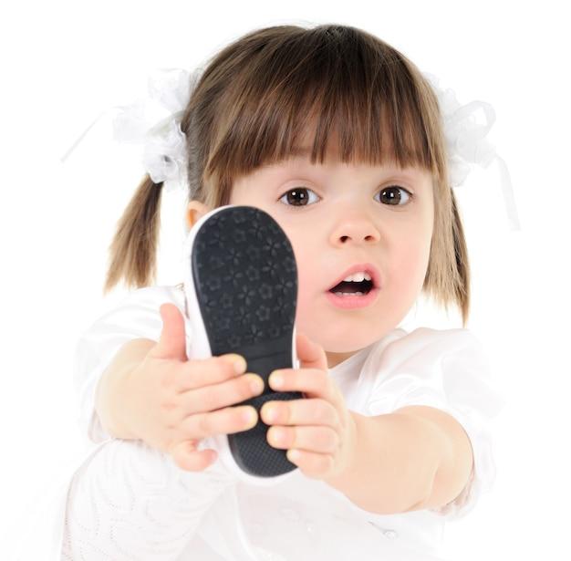La bambina in bei vestiti bianchi tiene il piede nelle mani in primo piano