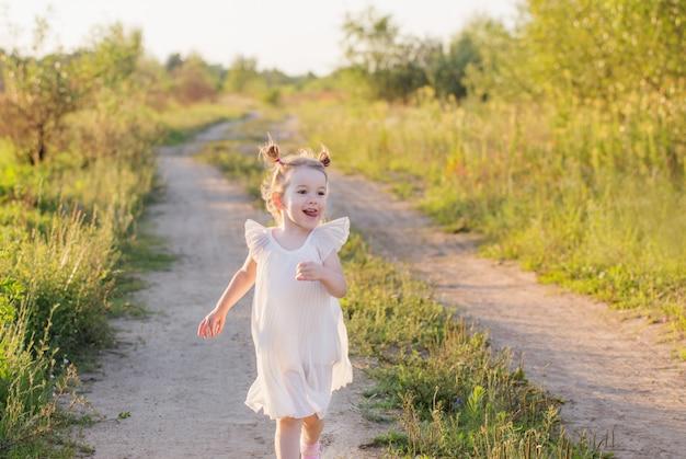 Bambina in vestito bianco all'aperto