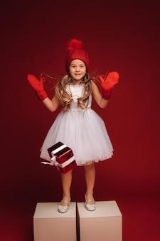 Una bambina con un vestito bianco e un cappello rosso lancia un regalo sul pavimento su uno sfondo rosso.