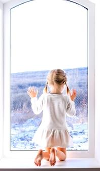 Una bambina con un vestito bianco si siede vicino alla finestra e guarda la foresta invernale
