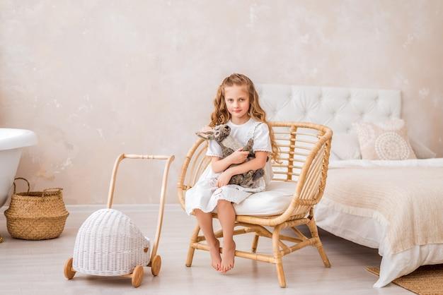 La bambina in un vestito bianco si siede su una sedia e abbraccia un coniglietto di pasqua. un bambino in una stanza luminosa con un coniglio giocattolo.