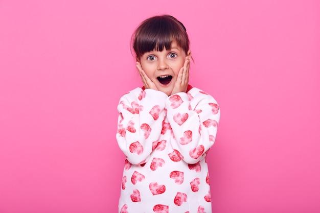 Bambina in maglione bianco con cuori, ha ultime notizie, che copre le guance con i palmi, che guarda l'obbiettivo con espressione sorpresa, isolata sopra il muro rosa.