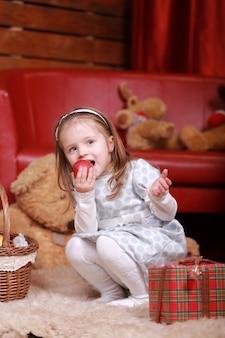 Bambina in abito bianco a pois mangia mela e divertirsi nello studio di natale. albero di natale, orsacchiotto e cesto con doni sul davanti.