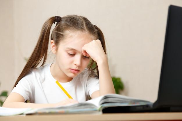 La bambina in una maglietta bianca fa i compiti. camera luminosa con luce del giorno, ragazza indipendente, istruzione