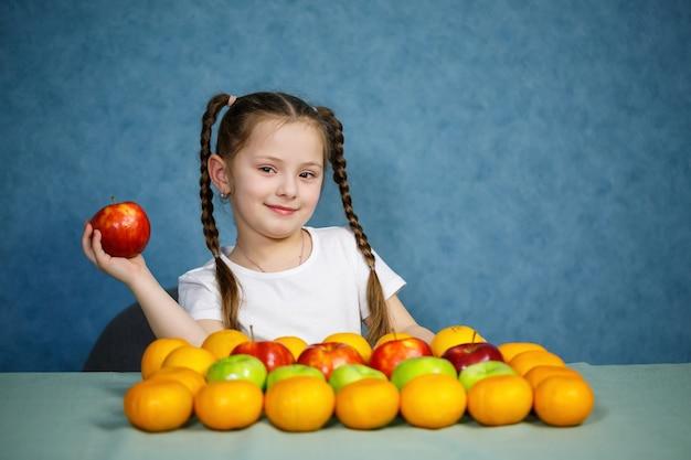 La bambina in maglietta bianca ama la frutta