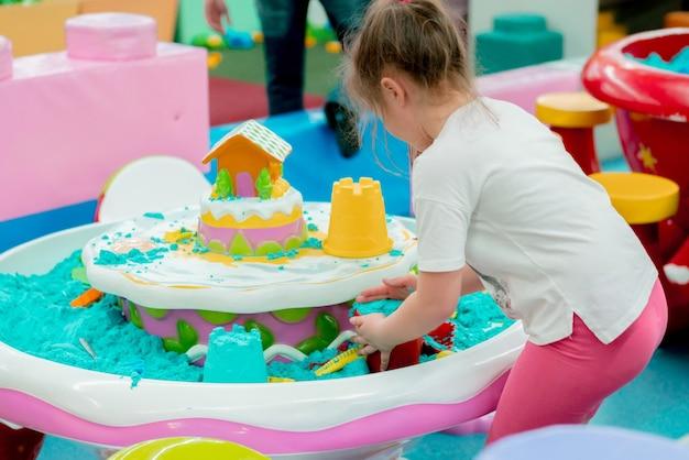 Bambina in maglietta bianca e pantaloni rosa che gioca con la sabbia cinetica blu nel parco giochi al coperto