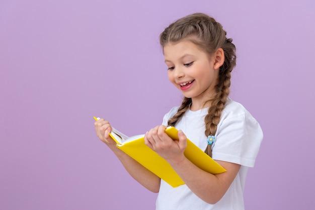 Una bambina con una maglietta bianca legge un libro su uno sfondo viola isolato