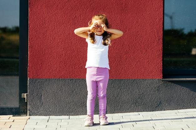 Bambina in maglietta bianca. spazio per il tuo logo o design. mockup per la stampa