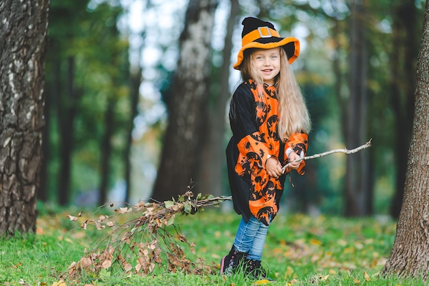 La bambina in costume da strega vola su un manico di scopa nel parco per le vacanze di halloween.