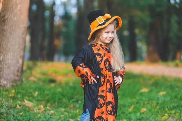 Bambina in costume da strega si trova nel parco in autunno durante le vacanze di halloween.