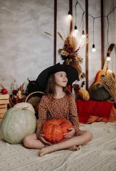 Una bambina con un cappello da strega è seduta su una coperta a maglia con zucche