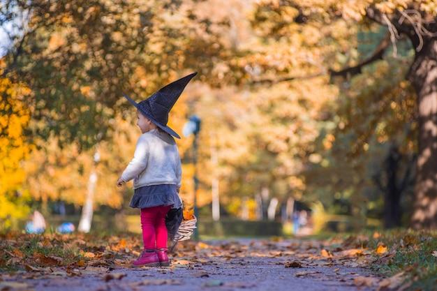 Strega bambina cammina nella foresta autunnale con un cesto di foglie.