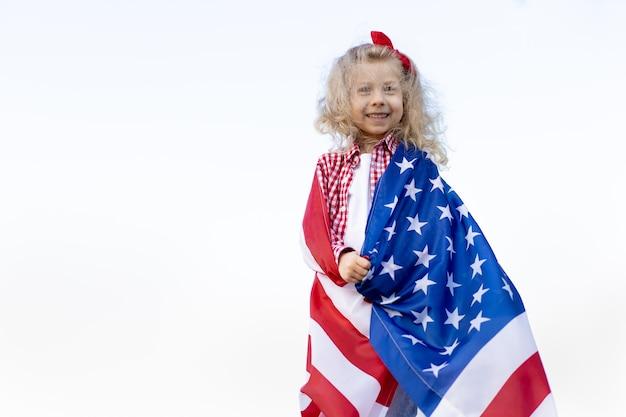 Una bambina con una bandiera americana su sfondo bianco, il concetto di patriottismo e il giorno dell'indipendenza degli stati uniti. giornata dei veterani degli stati uniti.