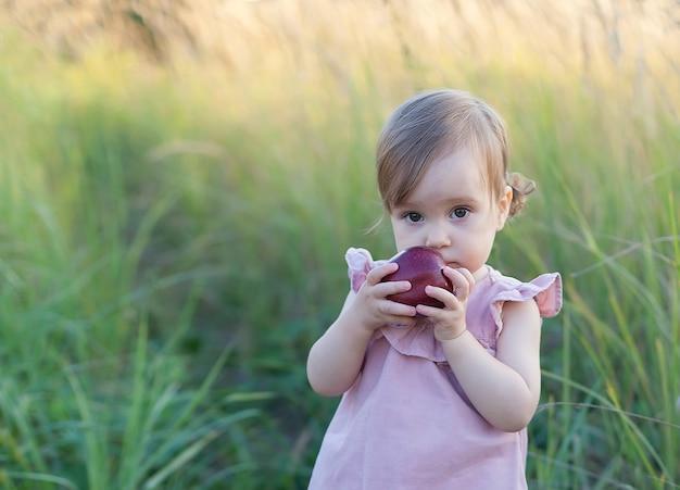 Una bambina con una mela in mano sta in un campo in una sera d'estate.