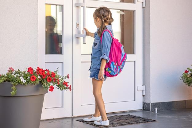 Una bambina con uno zaino, una scolaretta apre le porte della scuola.