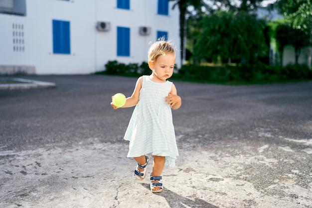 Bambina con una palla in mano cammina sull'asfalto sullo sfondo della casa