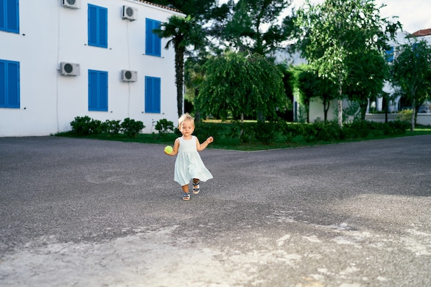 La bambina con una palla in mano cammina lungo il cortile asfaltato della casa
