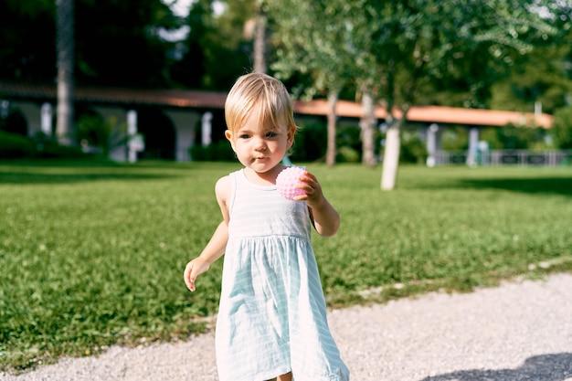La bambina con una palla in mano cammina lungo il sentiero di ghiaia nel parco