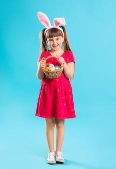 Bambina con cesto di uova di pasqua e orecchie di coniglietto sul colore