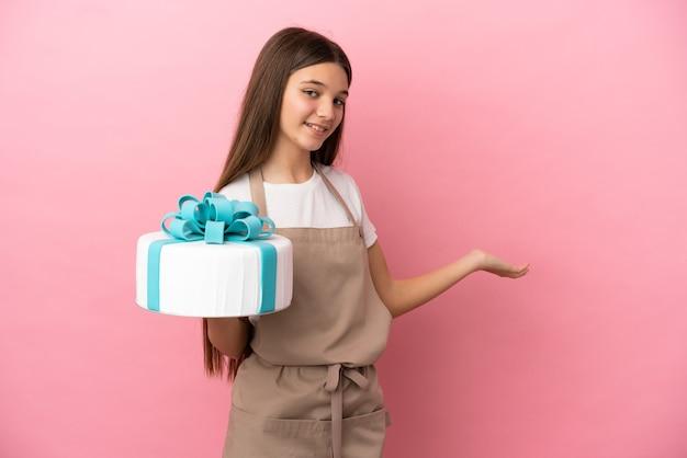 Bambina con una grande torta su sfondo rosa isolato che allunga le mani di lato per invitare a venire