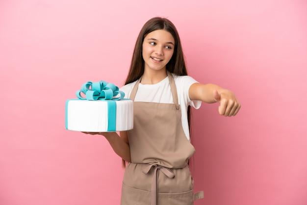Bambina con una grande torta su sfondo rosa isolato che fa un gesto di pollice in alto