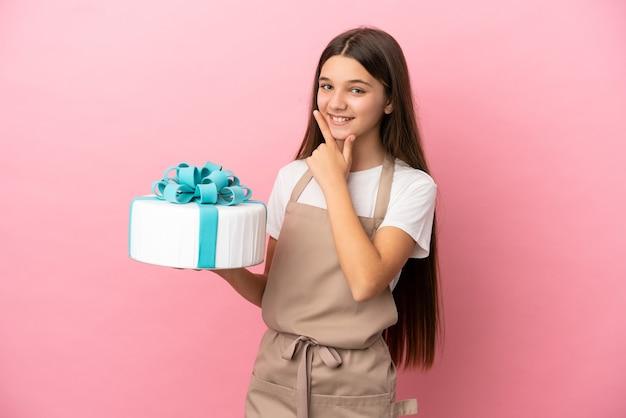 Bambina con una grande torta su sfondo rosa isolato felice e sorridente