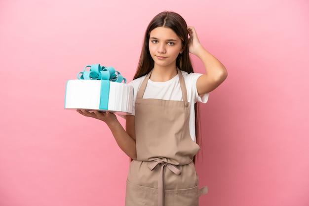 Bambina con una grande torta su sfondo rosa isolato che ha dubbi