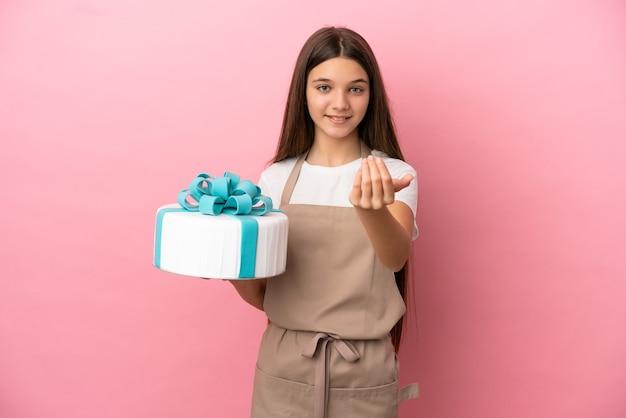 Bambina con una grande torta su sfondo rosa isolato che invita a venire con la mano. felice che tu sia venuto