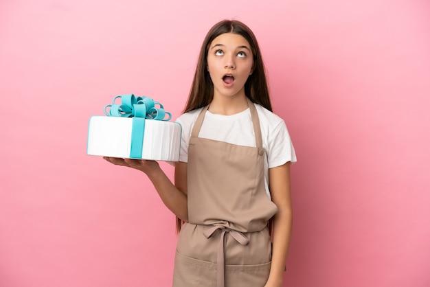 Bambina con una grande torta su sfondo rosa isolato guardando in alto e con espressione sorpresa